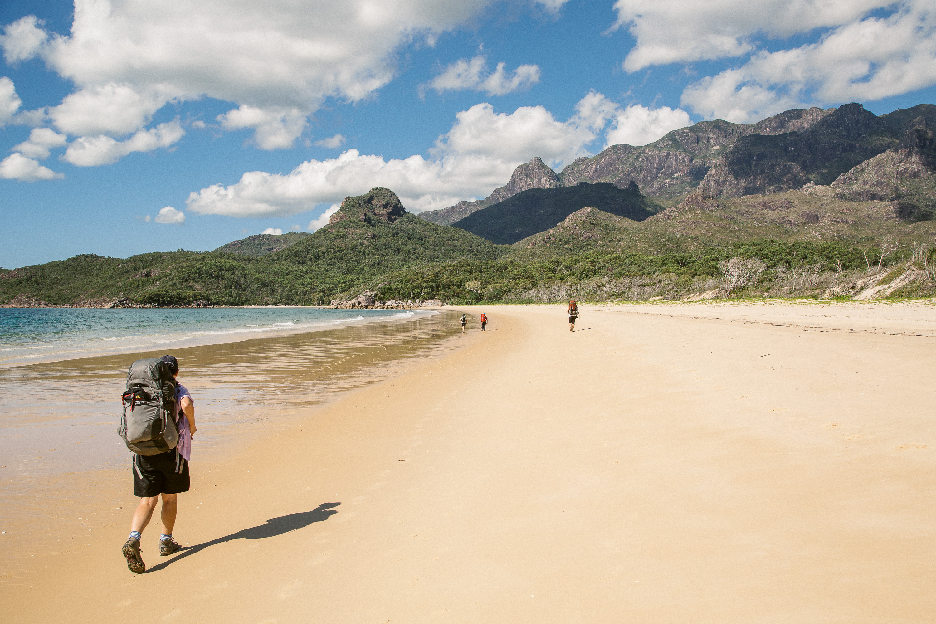 Walkers commence a 4 day hike on the Thorsborne Trail by crossing the beach at Ramsay Bay. The Thorsborne Trail is a 40km hiking path that visits several of Hinchinbrook Island's beaches and waterfalls. Situated off the coast of North Queensland, Australia, Hinchinbrook Island is a mountainous National Park characterised by rainforest and golden beaches. Walkers typically take 4 days to complete the hike, and to protect the ecosystem of the island only 40 visitors are allowed onto the trail at any one time.